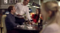 MS Man and woman talking in restaurant, waiter serving food
