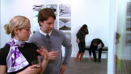 Man and woman talking over drinks at gallery opening / man reading newspaper on bench in background / woman sitting down next to man on bench / couple getting off bench and walking offscreen / couple in foreground shaking hands
