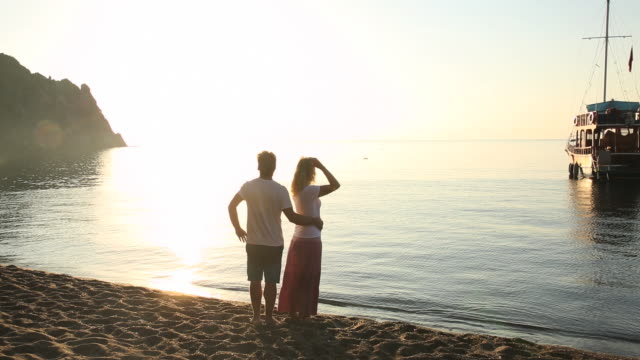 Man and woman walk along beach edge at sunrise, pausing to look out
