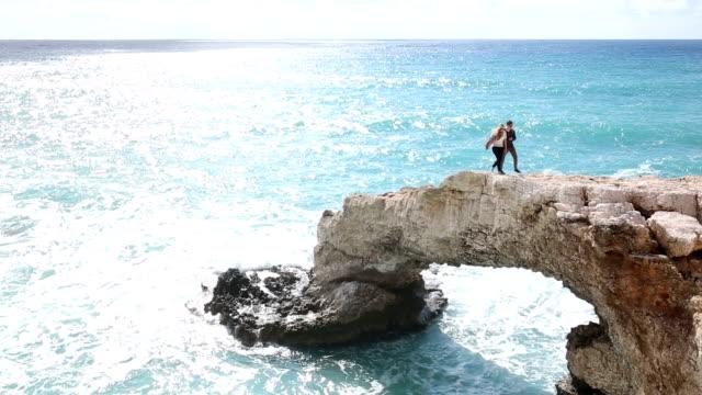 Man and woman walk along crest of natural rock bridge