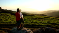 Man and woman walk along grassy crest above hills