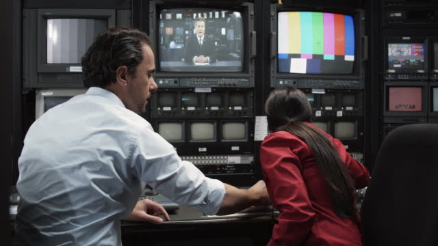 MS Man and woman working in television broadcasting control room, Dallas, Texas, USA