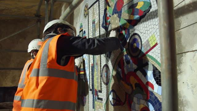 MS Man and woman working on mosaic renovation at Tottenham Court Road Underground Station / London, England, United Kingdom