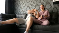 Man and woman young couple are playing video games and having fun on the couch