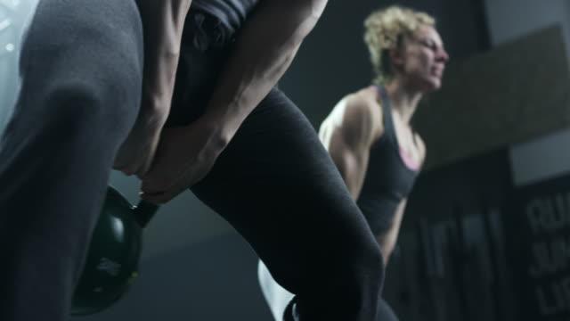 Man en vrouw doen oefening met de kettlebell in sportschool
