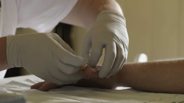 Man applies bandage on fresh wound, slow motion