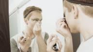 Man applying eye liner in mirror