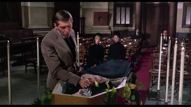 Man (James Coburn) approaches funeral casket and places mirror under corpse's nose before saying goodbye
