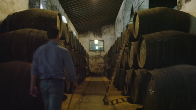 man approaches ladder leaning against stack of wooden wine barrels, climbs up and leans over to check level in barrel
