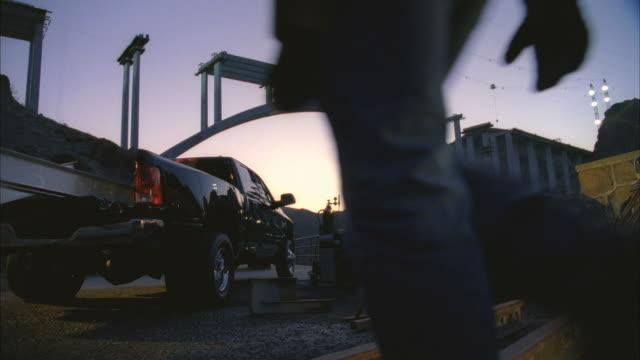 WS PAN Man arc welding next to truck beside construction bridge at Hoover dam / Boulder City, Nevada, USA