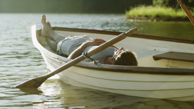 MS of man asleep in rowing boat on lake