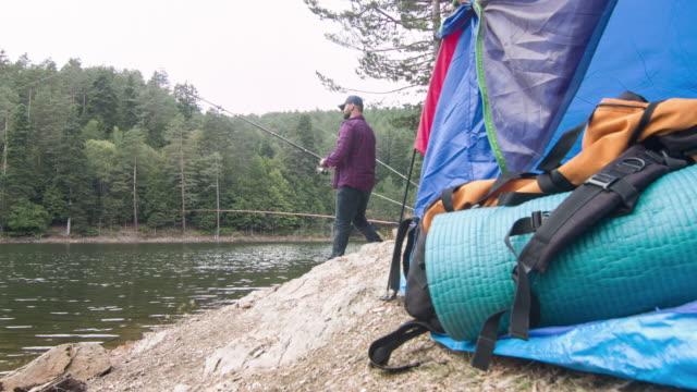 Man at campground fishing in lake