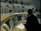 Man at Dungeness B Power Station control room completing paperwork at desk in front of monitors and panels of switches and gauges