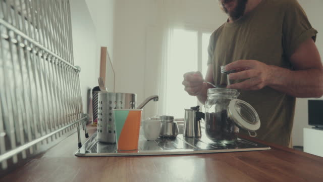 Man at home, preparing coffee in moka
