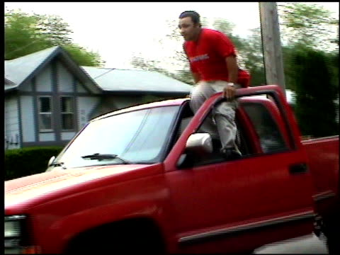 / man attempts to get out of red truck and sit on the roof of it while it's moving down the road / truck crashes into telephone pole Man attempts...