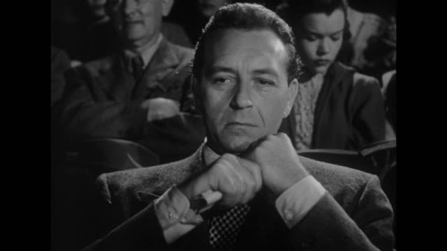 Man (Paul Henreid) attends the theater in order to watch his body double in action