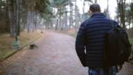 Man backpacker walking along a country road