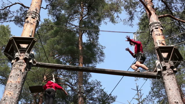 Man balancing on High Ropes course beam