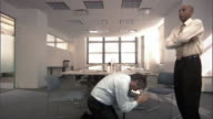 Man begging on knees in front of another man in conference room / standing man leaving room / pleading man following on knees