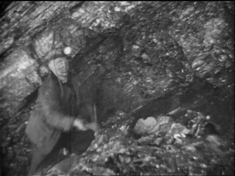 B/W 1938 man breaking off pieces of coal with pick axe in mine