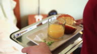 CU Man bringing orange juice and muffin on tray to woman lying in bed, Hoboken, New Jersey, USA