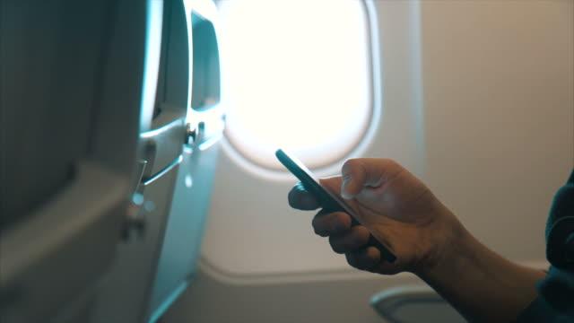 Mann Surfen Smartphone auf dem Flugzeug