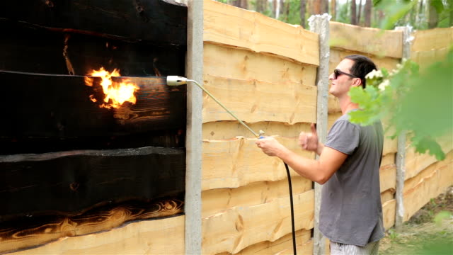 Man burns the surface of the wooden fence.