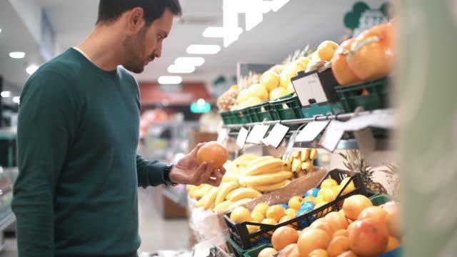 Man fruit in de supermarkt kopen.