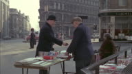1966 MS Man buying newspaper on street book stall / London, United Kingdom