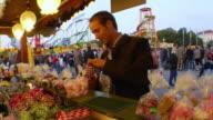 SLO MO man buying roasted almonds at Oktoberfest fair / Munich, Bavaria, Germany