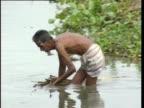 A man carries a bundle of reeds through a lake