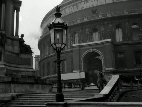 A man carrying a cello walks down steps outside the Royal Albert Hall