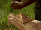 Man carves crocodile head into prow of dugout canoe, Papua New Guinea