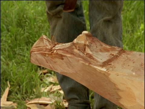 Man carves crocodile head into prow of dugout canoe, Papua New Guinea