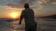 MS Man casting fly rod in surf at sunset / Iztapa, Guatemala