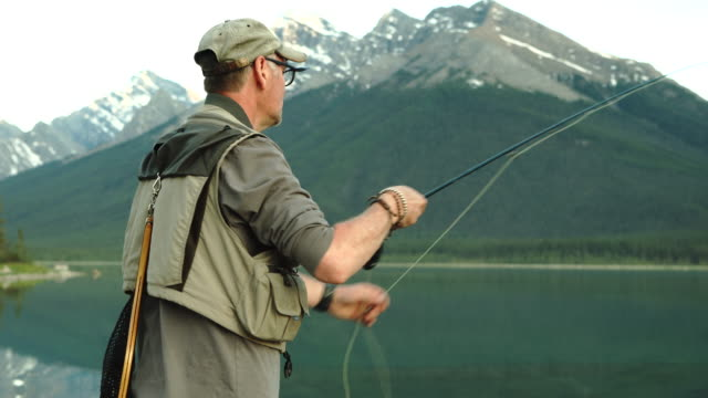 Man casts fly fishing line into mountain lake, near inlet stream