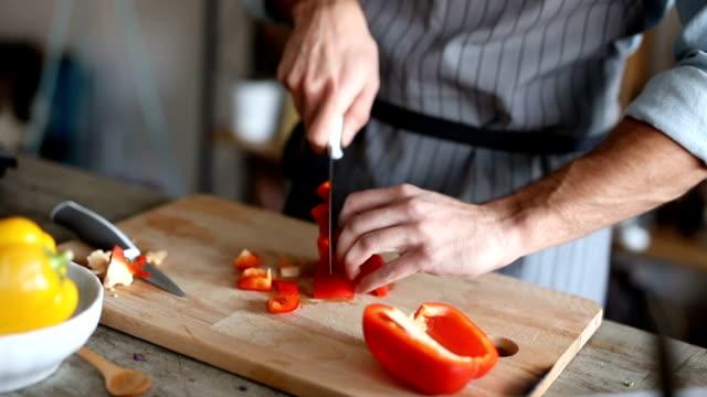 Man hakken rode paprika in blokjes