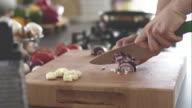 Man chopping red onion on cutting board