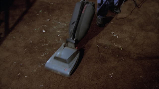 MS Man cleaning dirty dark brown carpet by vacuum cleaner / Unspecified