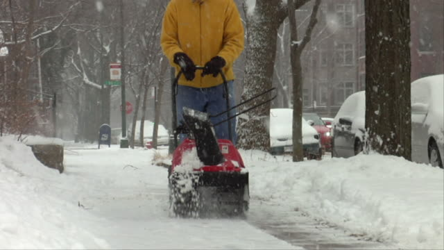 WS CU Man cleaning snow from sidewalk with snow blower / Chicago, Illinois, USA