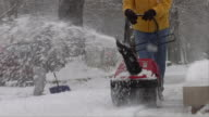 MS Man cleaning snow from sidewalk with snow blower, mid section / Chicago, Illinois, USA
