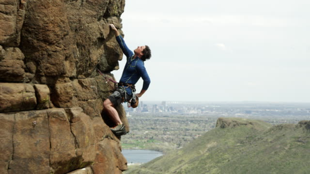 Man climbs a steep rock face with the city of Denver in the background.