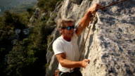 Man climbs vertical rock cliff