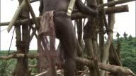 Man climbs wooden tower during land diving ritual, Pentecost, Vanuatu