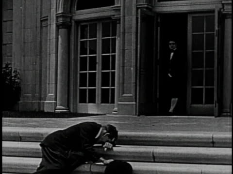 1920 MONTAGE Man collapsing in despair on steps of his darling's home while butler shakes out dirty rug over him and men brawl inside