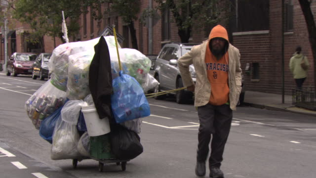 Man collecting tin cans, New York City, USA