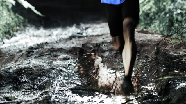TD Man competing in a night trail run running across a puddle