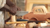 A man constructs a wooden model of a car.