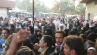 A man controls a crowd with a taser as people push and shove outside a bakery in Aleppo Syria / Bread was scarce and lines long