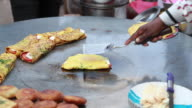 Man cooking moong dal chilla in the market, Delhi, India